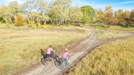 Family on bikes autumn cycling outdoors, active mother and kid on bicycles, aerial view of happy family with child in fall park from above, sport and fitness concept