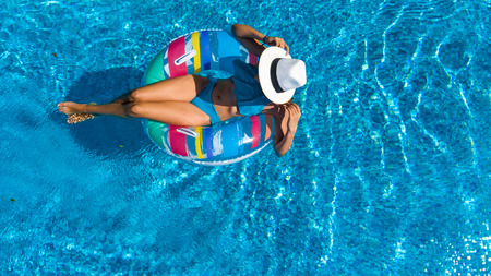 Beautiful girl in hat in swimming pool aerial drone view from above, woman relaxes and swims on inflatable ring donut and has fun in water on family vacation, tropical holiday resort
