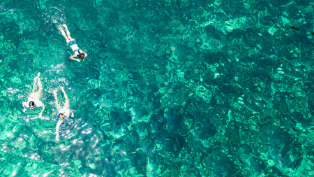 Aerial top view of family snorkeling from above, mother and kids snorkelers swimming in a clear tropical sea water with corals during summer vacation in Thailand Standard-Bild