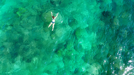 Aerial top view of woman snorkeling from above, girl snorkeler swimming in a clear tropical sea water with corals during summer vacation in Thailand