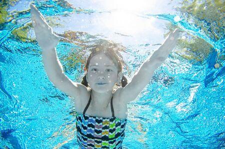 Kind zwemt onder water in zwembad, gelukkig actief tienermeisje duikt en heeft plezier onder water, kind fitness en sport op familievakantie op resort