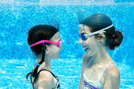 Kinder schwimmen im Schwimmbad unter Wasser, glückliche aktive Mädchen haben Spaß unter Wasser, Kinderfitness und Sport im aktiven Familienurlaub