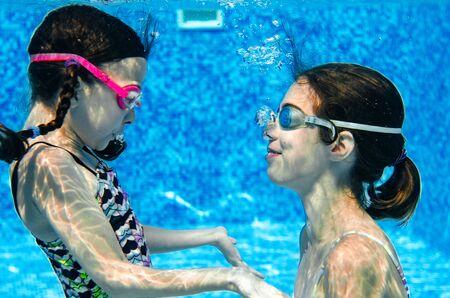 Kinder schwimmen im Schwimmbad unter Wasser, glückliche aktive Mädchen haben Spaß unter Wasser, Kinderfitness und Sport im aktiven Familienurlaub Standard-Bild