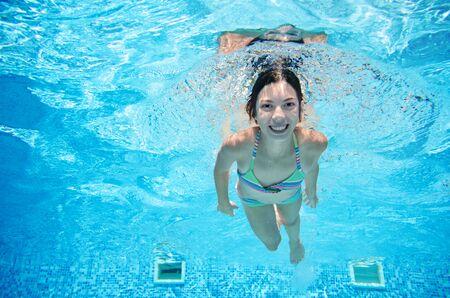 Kind schwimmt unter Wasser im Schwimmbad, glückliches aktives Teenagermädchen taucht und hat Spaß unter Wasser, Kinderfitness und Sport im Familienurlaub im Resort