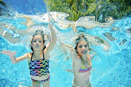 Children swim underwater in swimming pool, happy active girls have fun under water, kids fitness and sport on active family vacation