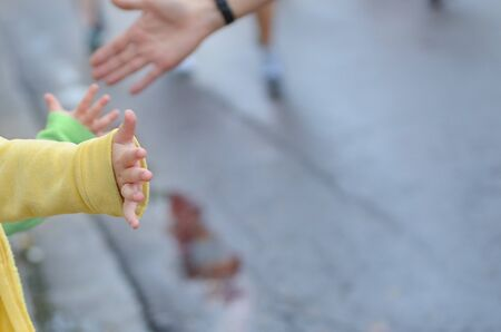 Marathon running race,runners support on road race, child's hand giving highfive, kid supporting athletes who run, sport concept