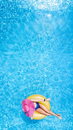 Beautiful woman in hat in swimming pool aerial top view from above, young girl in bikini relaxes and swims on inflatable ring donut and has fun in water on family vacation, tropical holiday resort