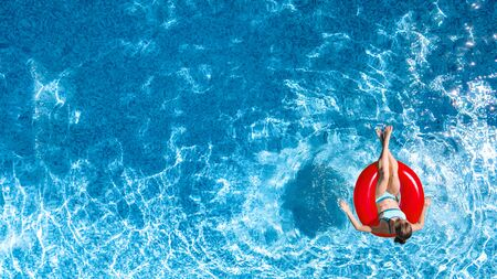 Active young girl in swimming pool aerial top view from above, child relaxes and swims on inflatable ring donut and has fun in water on family vacation, tropical holiday resort Stock Photo