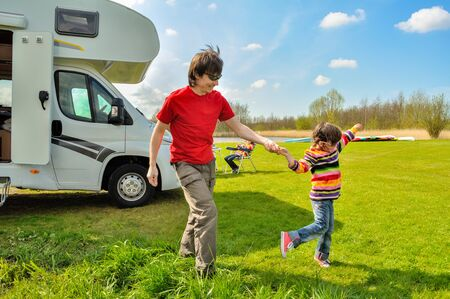 Family vacation, RV travel with kids, happy father with child has fun on family holiday trip in motorhome, camper exterior