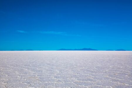 Landscape of Salar de Uyuni in Bolivia covered with water, salt flat desert and sky reflections