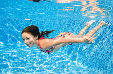 Child swims underwater in swimming pool, little active girl dives and has fun under water, kid fitness and sport on family vacation on resort