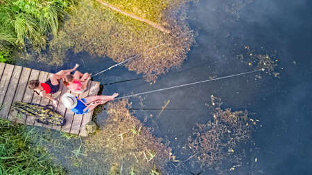Happy family and friends fishing together outdoors near lake in summer, aerial top view from above Imagens