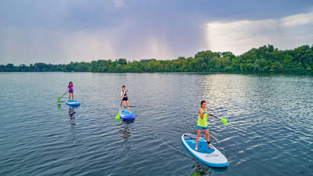 Active family on SUPs, standing up paddleboards, in river water, summer family sport, aerial top view from above
