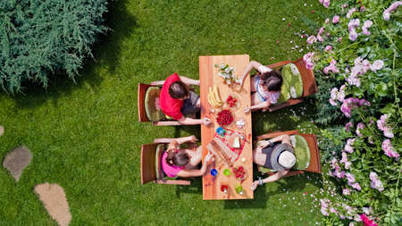 Family and friends eating together outdoors on summer garden party. Aerial view of table with food and drinks from above. Leisure, holidays and picnic concept Archivio Fotografico