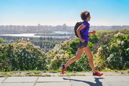 Woman runner run commutes to work with backpack, city morning run commuting and fitness concept, Kiev, Ukraine Zdjęcie Seryjne
