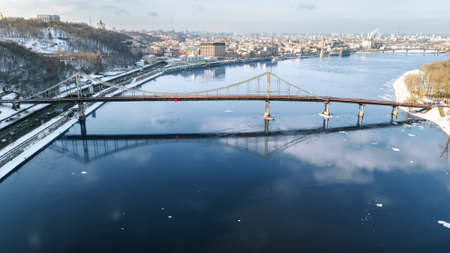 Aerial top view of pedestrian Park bridge in winter, Dnieper river and Podol district from above, snow Kyiv cityscape, city of Kiev skyline, Ukraine