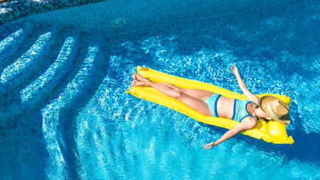 Girl relaxing in swimming pool, child swims on inflatable mattress and has fun in water on family vacation, tropical holiday resort, aerial drone view from above Reklamní fotografie
