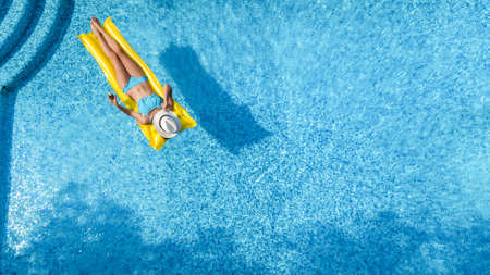 Beautiful young girl relaxing in swimming pool, woman swims on inflatable mattress and has fun in water on family vacation, tropical holiday resort, aerial drone view from above Standard-Bild