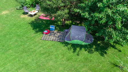 Campsite aerial view from above, tent and camping equipment under tree, family vacation in camp outdoors concept