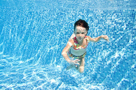 Little child swims underwater in swimming pool, happy active girl dives and has fun under water, kid fitness and sport Standard-Bild
