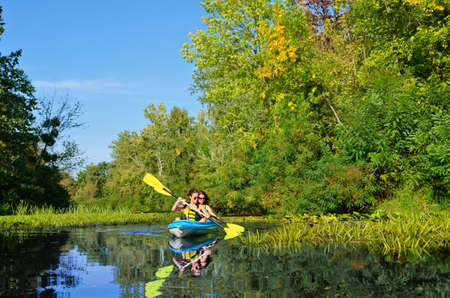 Family kayaking, mother and daughter paddling in kayak on river canoe tour having fun, active weekend and vacation with children, fitness concept