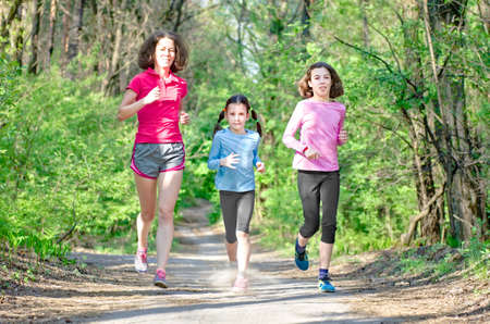 Family running, happy active mother and kids jogging outdoors, run with children in forest, healthy family sport and fitness
