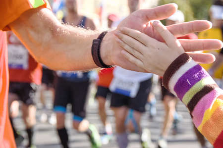 Marathon running race, supporting runners on road, child hand giving highfive, sport concept