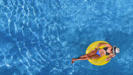 Beautiful woman in hat in swimming pool aerial view from above, young girl relaxes and has fun on inflatable ring in water on vacation