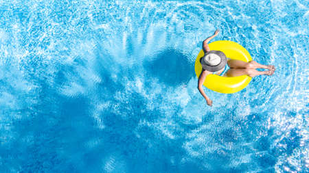 Active young girl in swimming pool aerial top view from above, child relaxes and swims on inflatable ring donut and has fun in water on family vacation, tropical holiday resort Standard-Bild
