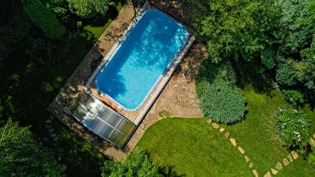 Swimming pool in beautiful garden aerial top view Standard-Bild