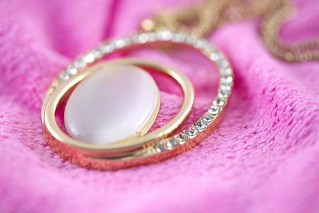 diamond necklace: Necklace Diamond gold on fabric pink. Stock Photo