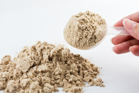 whey: The hand raise a spoon measure Whey protein chocolate powder for fitness and bodybuilding gaining muscle.