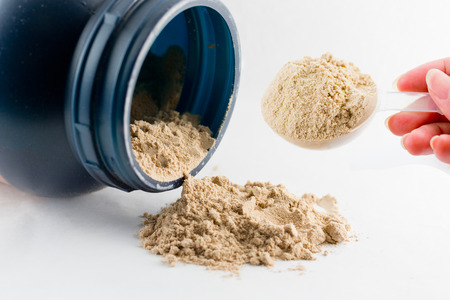 The hand raise a spoon measure Whey protein chocolate powder for fitness and bodybuilding gaining muscle.