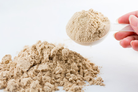 gaining: The hand raise a spoon measure Whey protein chocolate powder for fitness and bodybuilding gaining muscle.