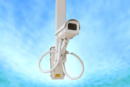 deterrent: Security camera isolated on blue sky background. Stock Photo