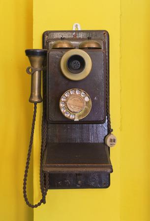 old desk: Antique vintage telephone yellow grunge background.