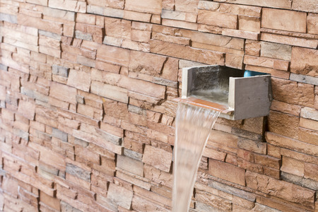 piped: Water fall drain with wall brick.
