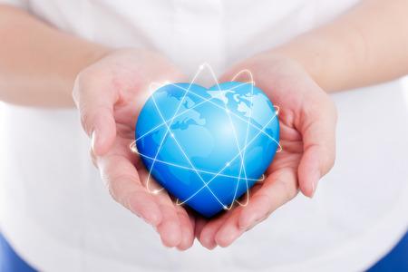 Female hands holding on earth global heart.