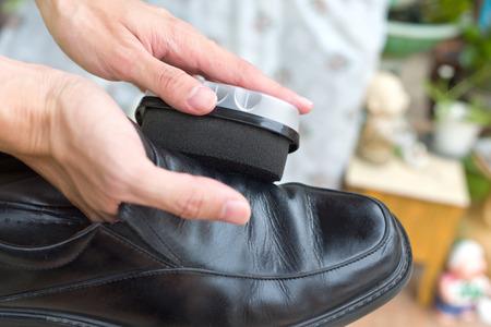 Hands polish leather black shoes.