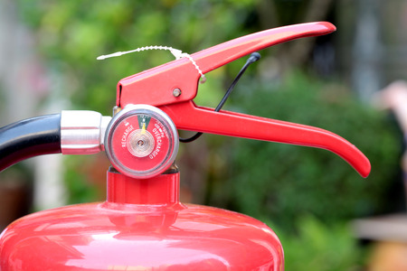 compression tank: Close- up Fire extinguisher red tank with green background.