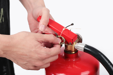 safety pin: Close- up Fire extinguisher and pulling pin on red tank. Stock Photo