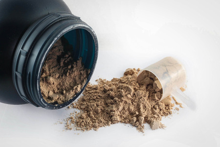 protein: Spoon measure Whey protein chocolate powder for fitness and bodybuilding gaining muscle. Stock Photo