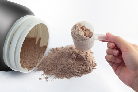 chocolate powder: The hand raise a spoon measure Whey protein chocolate powder for fitness and bodybuilding gaining muscle.