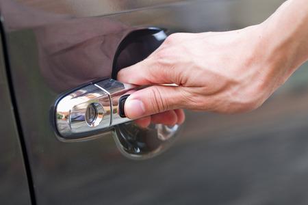 hand press: Hand press unlock button alarm system on black car .