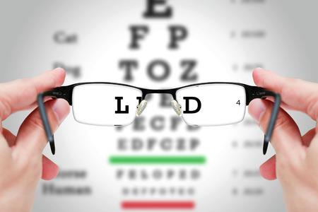 視力テスト グラフ基板上でメガネを保持している女性の手。