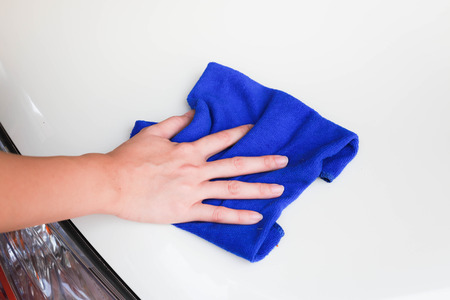 valeting: Female hand with microfiber cloth clean white car.