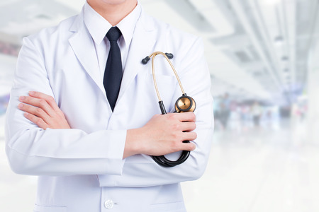 fold ones arms: Doctor stand fold ones arms with stethoscope office background.