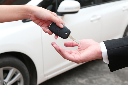 rent: Female hand giving a key for buyer or rental car.