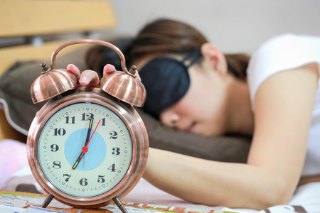 blindfold: Young women sleepy in bed with blindfold and closed clock.