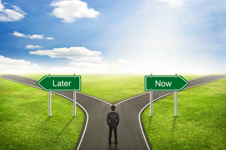 later: Businessman concept, Later or Now road to the correct way. Stock Photo
